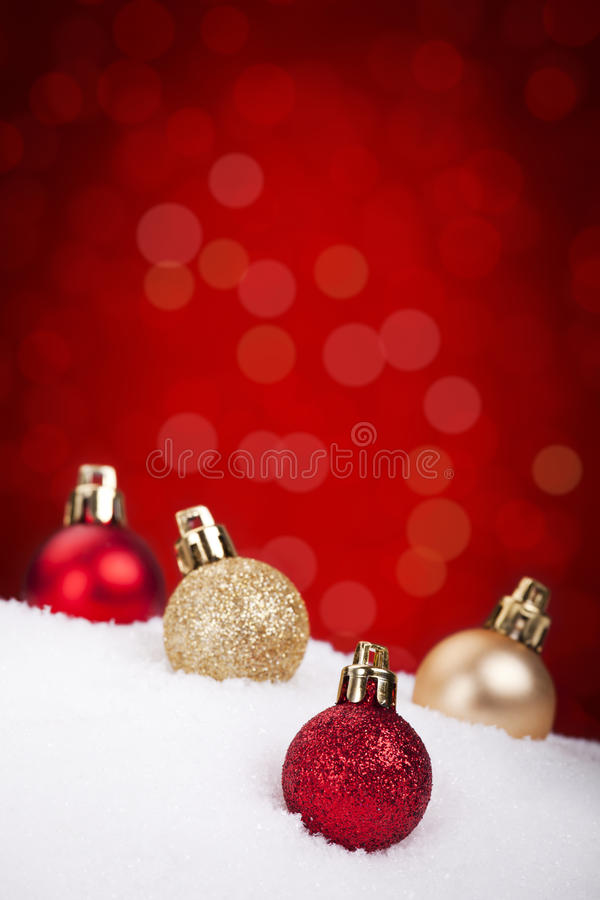 Red and gold Christmas baubles on snow, red background. Small red and gold Christmas baubles on snow with defocused red lights in the background. Shallow depth royalty free stock images