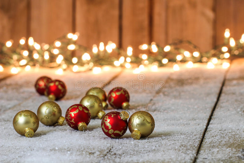 Red and gold Christmas ornaments on snowy background royalty free stock images