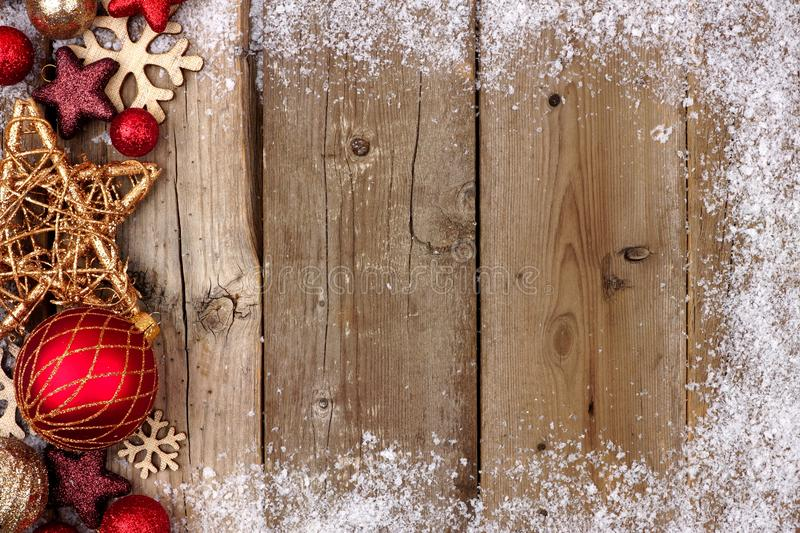 Red and gold Christmas side border with snow on wood. Red and gold Christmas ornament side border with snow frame on a rustic wood background royalty free stock photography