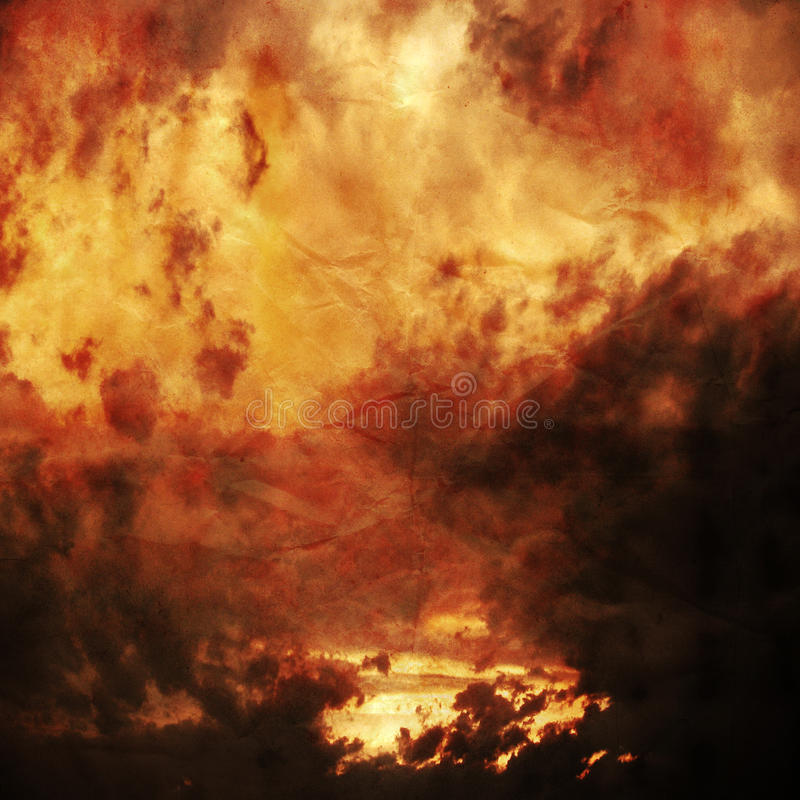 Red and Gold Clouds Paper Texture Background. Red and gold photographic sunset clouds on paper with visible creases, background texture wallpaper royalty free stock photo