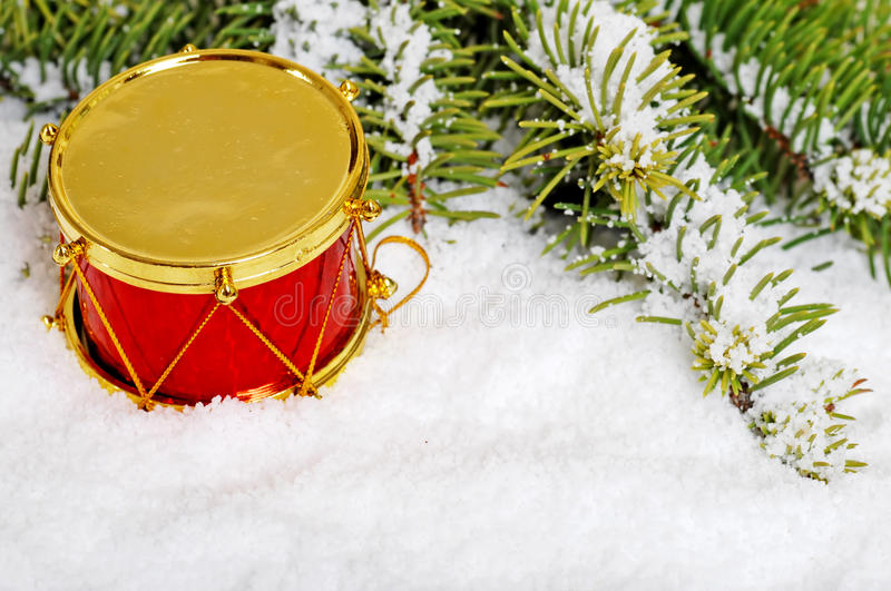Red and gold drum in snow. With spruce tree branch royalty free stock photography