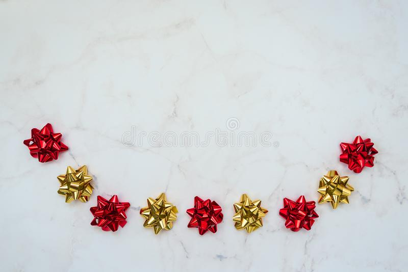 Red and gold festive bows on white marble background. Backdrop for cards, invitations, greetings.  royalty free stock photos