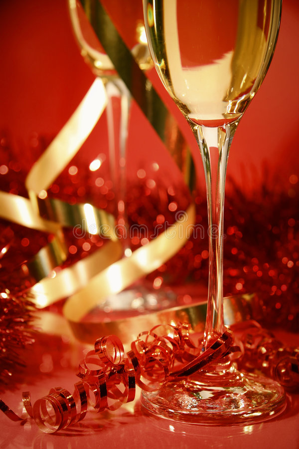 Red and gold sparkle. Fluted champagne glasses and ribbons on red background stock photography