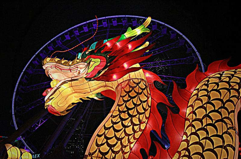 Red and golden dragon in front of Hong Kong Observation Wheel. The Hong Kong Observation Wheel is a 60-metre tall Ferris wheel located on the Central and Wan stock photography