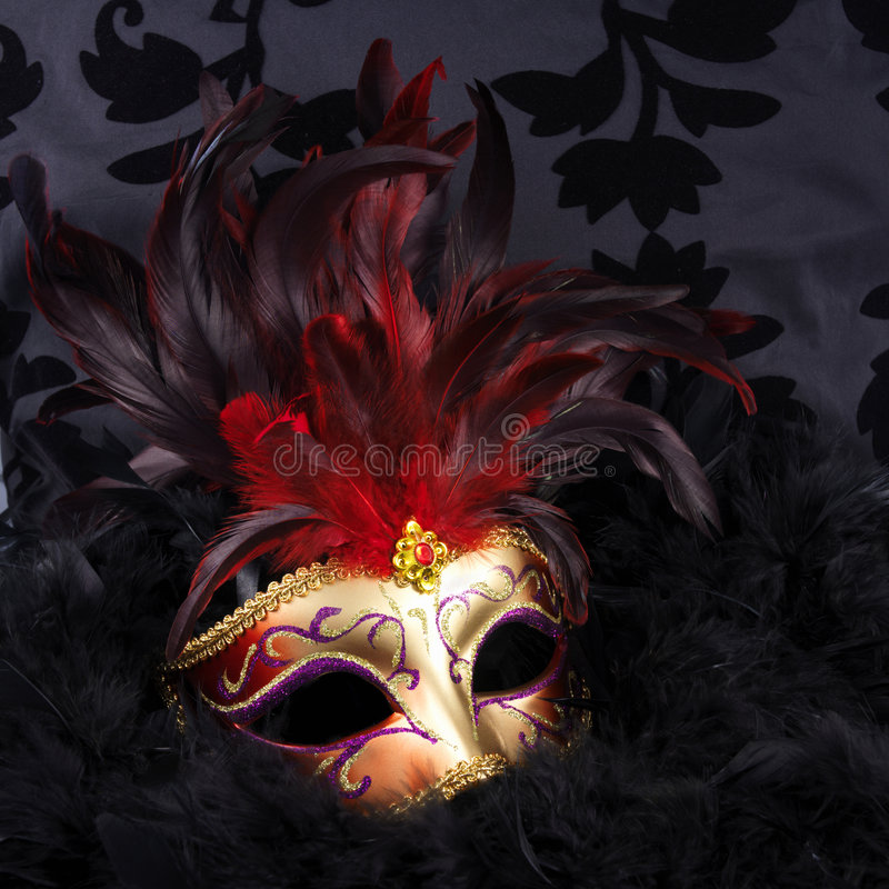 Red and golden mask with black feathers (Venice). On a black velvet background royalty free stock photography