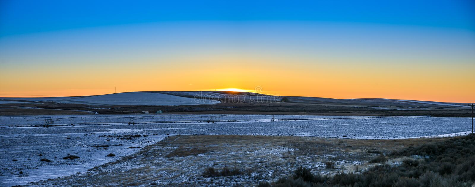 Red Golden Winter Sunset On The Horizon Of Hilly Snow Field Farmland Under Darken Blue Sky, Washington, United States. Vibrant golden-red sunset painted the royalty free stock photo