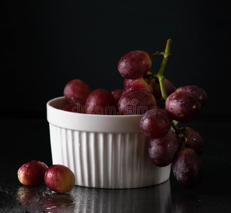 Red grape on the bowl dark front macro low key stock images