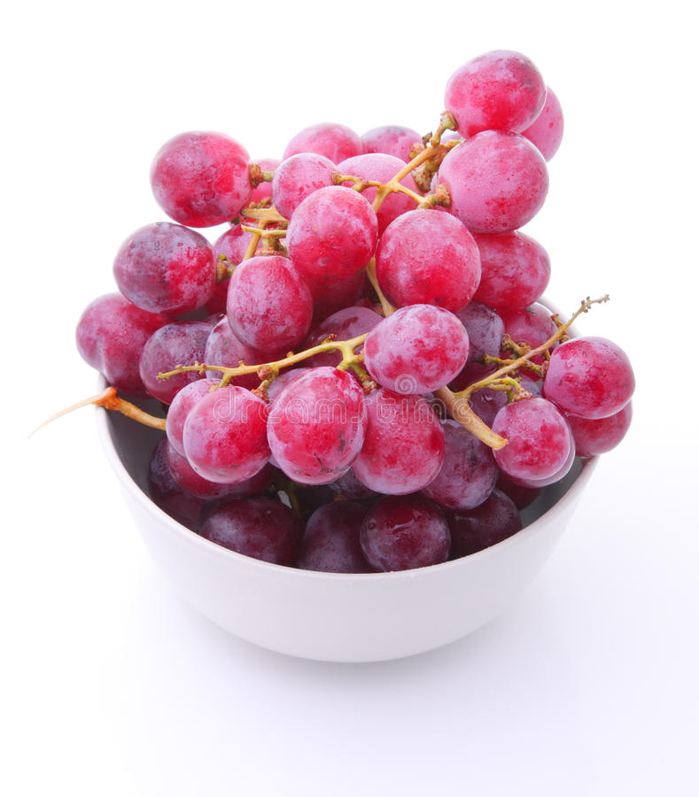 Red grape in bowl on white
