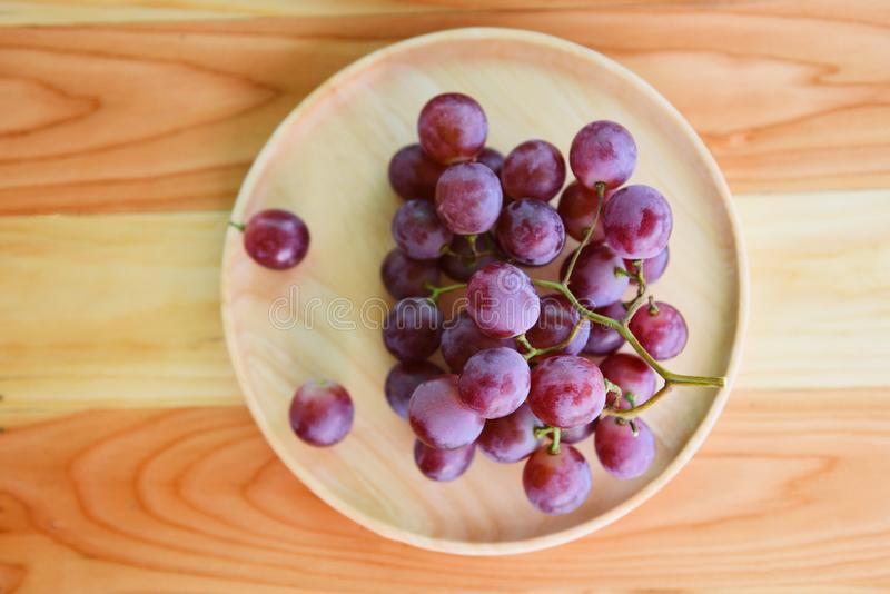 Red grape bunch on wooden plate on a table royalty free stock photography