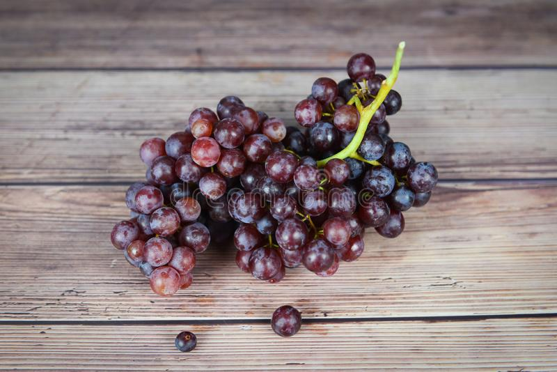 Red grape on wooden table - Bunch of grapes juicy fruit royalty free stock photography
