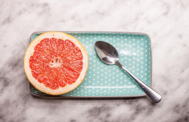 Red grapefruit rectangular plate and spoon. Red cut grapefruit blue rectangular plate on white marble background royalty free stock photo