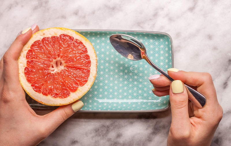 Red grapefruit rectangular plate and spoon. Red cut grapefruit blue rectangular plate on white marble background stock image