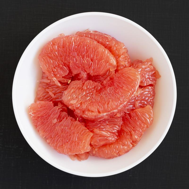 Red grapefruit slices in a white bowl on a black surface, overhead view. Flat lay, top view, from above. Close-up royalty free stock photos
