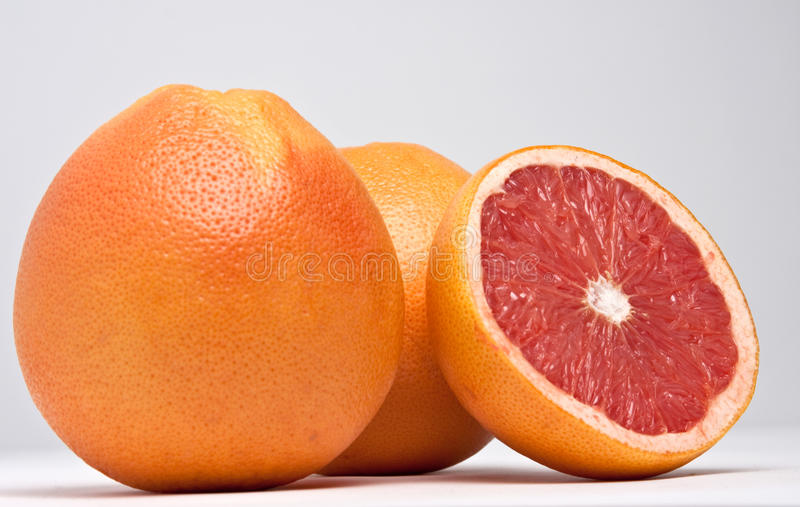 Red grapefruits. On light background , two and a half of them, raw,tiff,psd available royalty free stock image