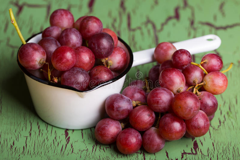 Red grapes in enamel pot on green background stock image