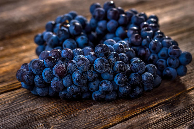 Red grapes. Organic red grapes on old wooden table royalty free stock photo