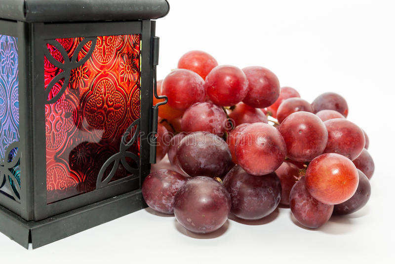 Red grapes and Ramadan lantern. On white background. Ramadan Eid concept background stock photos