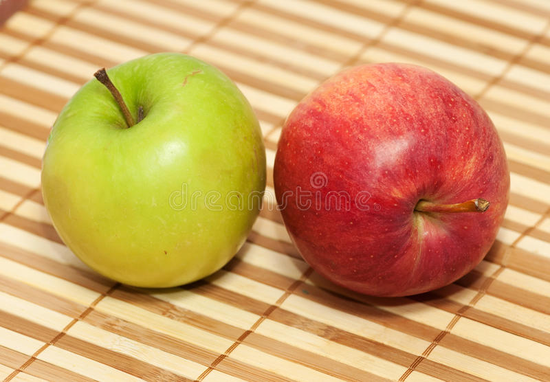 Red and green apple. On background wooden wicker striped napkin royalty free stock photo