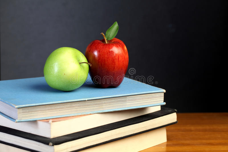 Red and green apple on text books royalty free stock photography