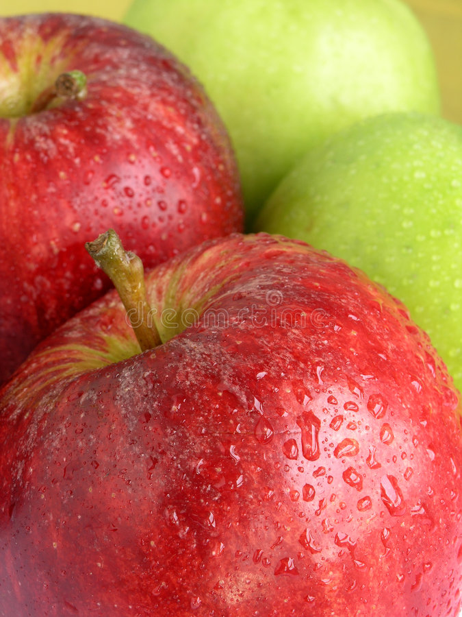 Red and green apples. Detail of red and green apples covered with droplets of water royalty free stock image