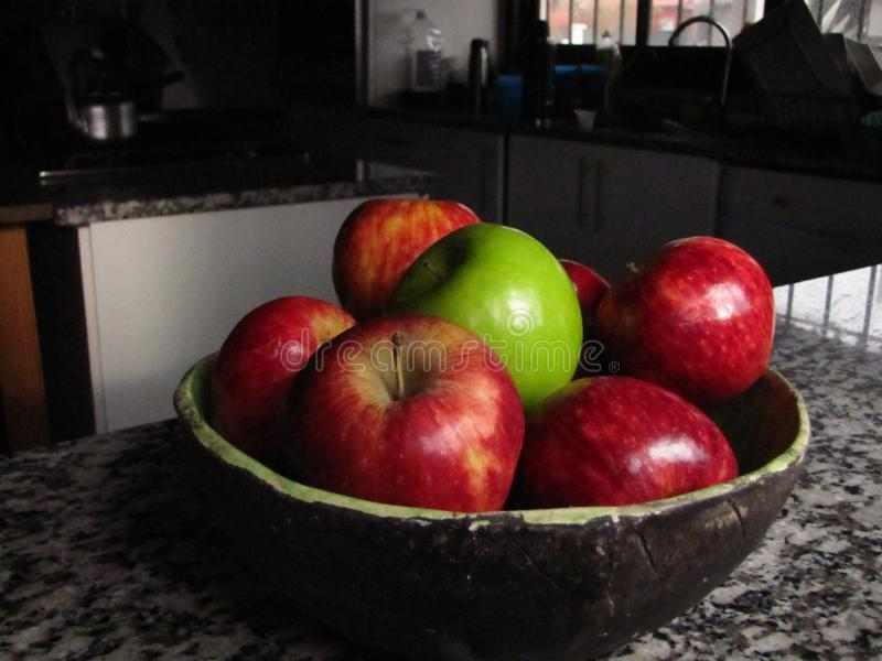 Red and green apples in a bowl royalty free stock images