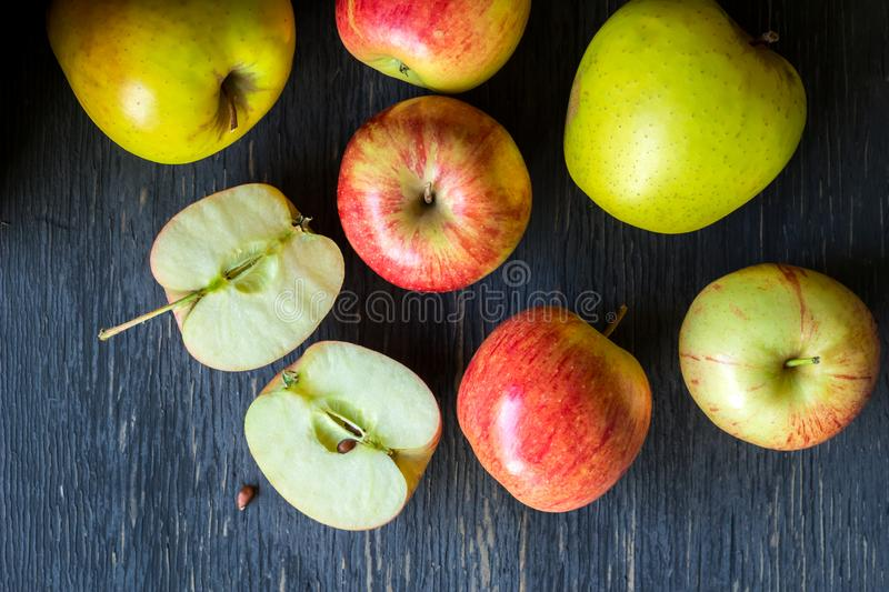Red and green apples on a dark wood background - overhead view. Red and green apples on a dark rough textured wood background - top view of star king and golden royalty free stock image
