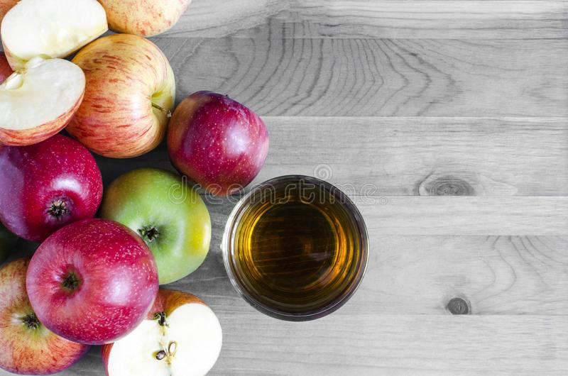 Red and green apples and transparent glass of Apple juice on black white background. Top view royalty free stock photo
