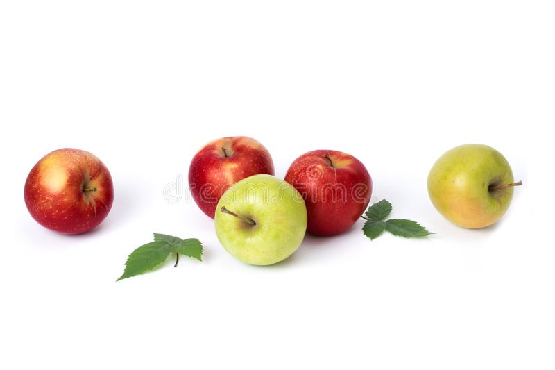Red and green apples on a white background. Green and red juicy apples with green leaves on an isolated background. A group of rip royalty free stock image