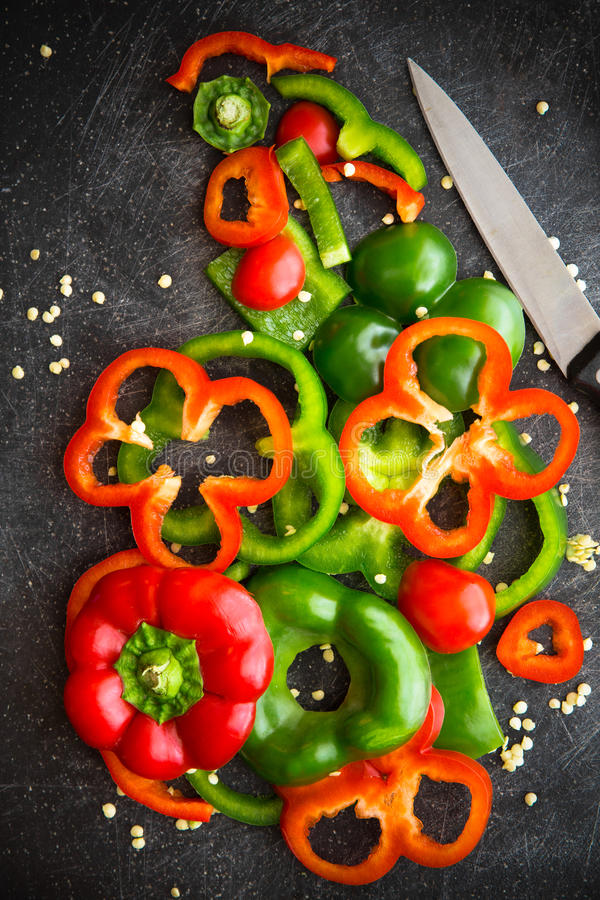 Red and Green Bell Peppers slices. Cutting board and knife with fresh organic red and green bell peppers sliced and chopped for meal preparation royalty free stock photo