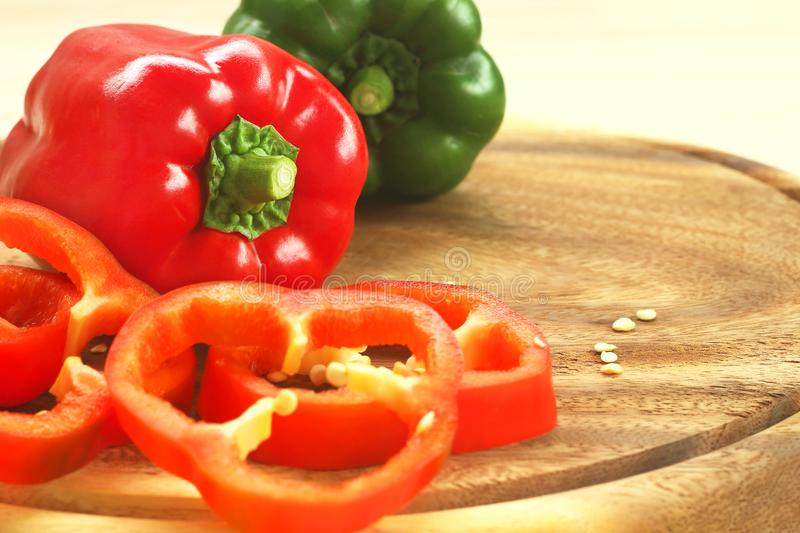 Red and green bell peppers on wooden cutting board with copy space royalty free stock photo