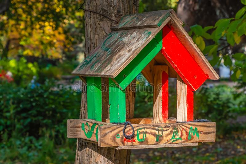A red and green bird and squirrel feeder house from boards is hanging on a brown tree. In a park in autumn royalty free stock photography
