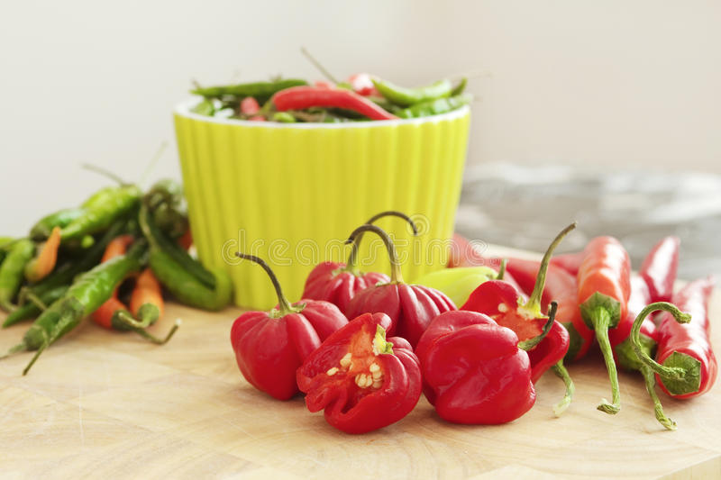 Red and green chilli peppers on a chopping board royalty free stock photos