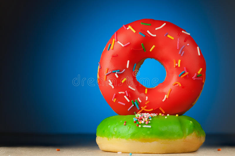 Red and green donuts on a blue background royalty free stock photo