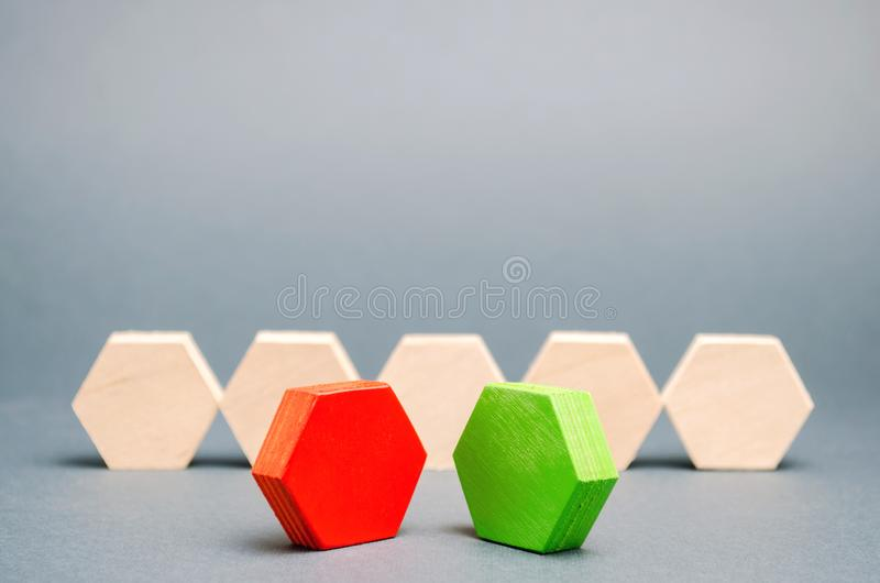 Red and green figurines stand in front of a crowd. Two opponents. Conflict of interest. Dispute. Search for compromises. Social. Problems. Business competition royalty free stock photo