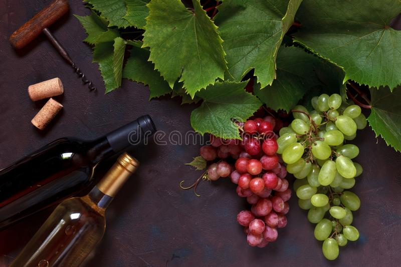 Red and green grapes with leaves, corks, corkscrew and two bottles of wine, white and red. Top view, close up on dark vintage stock image