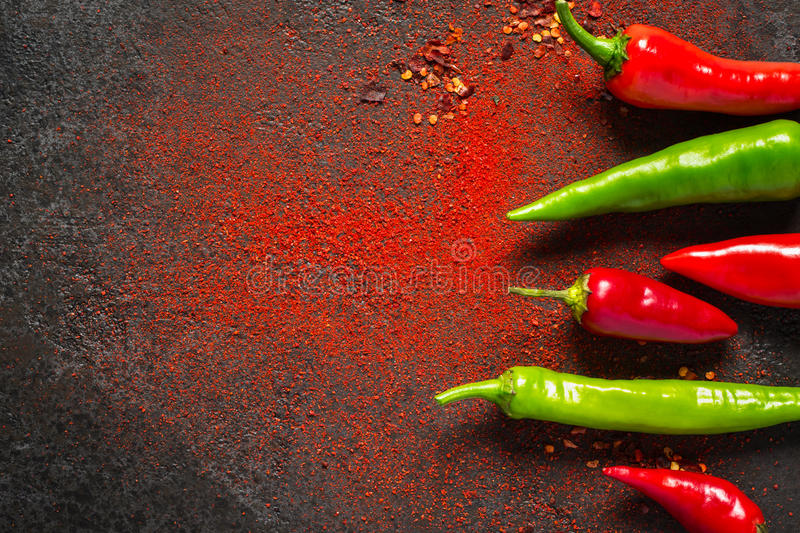 Red and green hot pepper and dry ground pepper on a dark background royalty free stock image