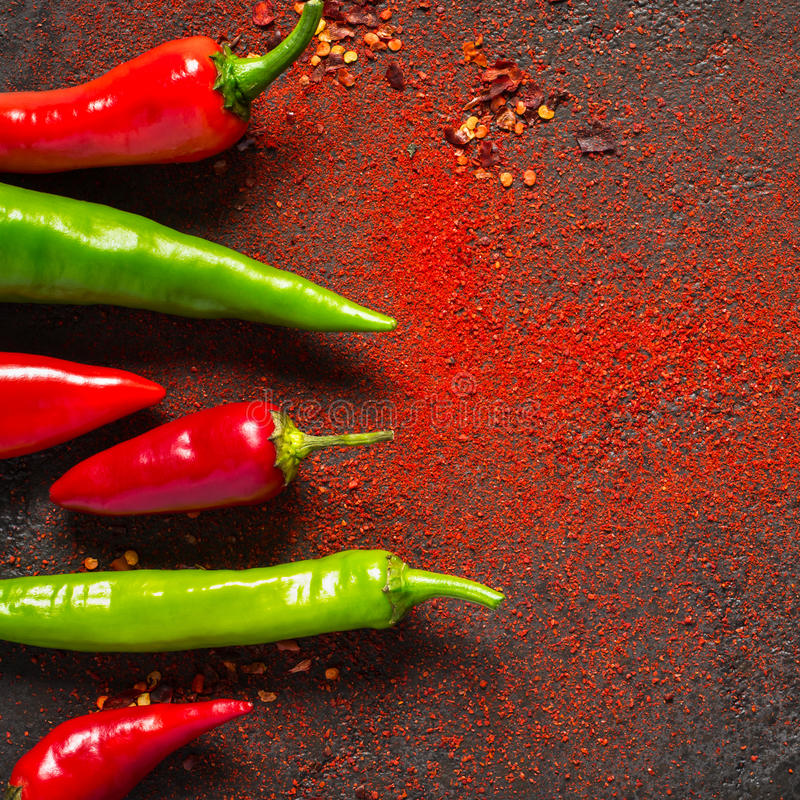Red and green hot pepper and dry ground pepper on a dark background.  royalty free stock photography