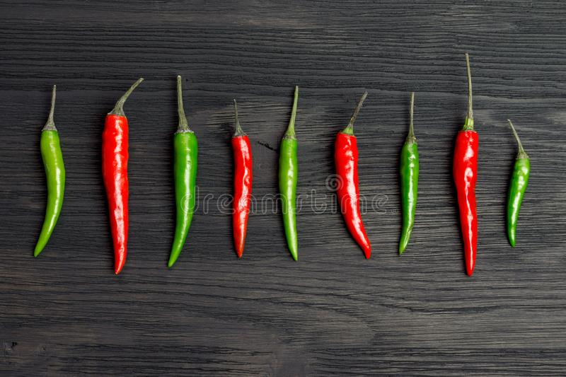 Red and green hot pepper. On a wooden table royalty free stock photography