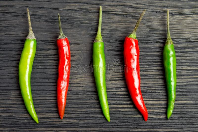 Red and green hot pepper. On a wooden table stock image