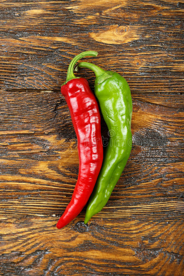 Red and green hot pepper on a wooden background. Red and green hot pepper lie on a brown wooden background, space for text, top view stock photos