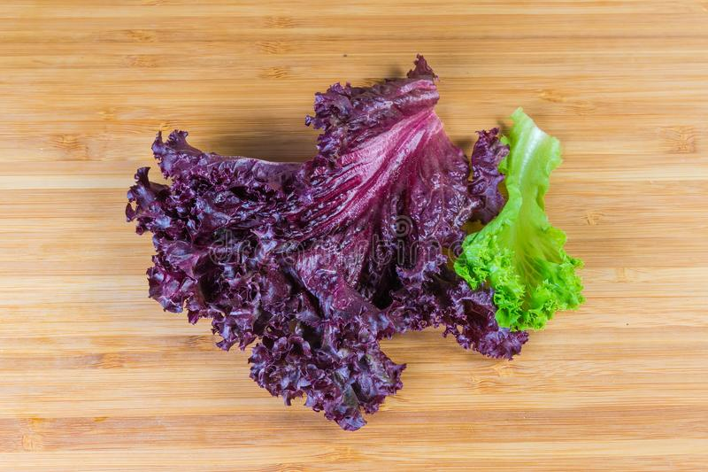 Red and green lettuce leaves on a wooden cutting board stock photos