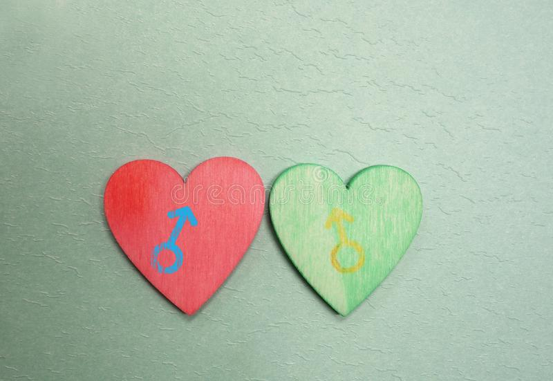 Red and green same sex hearts. Red and green painted hearts with male gender symbols royalty free stock photos