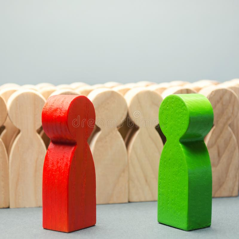 Red and green people stand in front of a crowd. Two opponents. Conflict of interest. Dispute. Search for compromises. Social. Problems. Business competition royalty free stock image