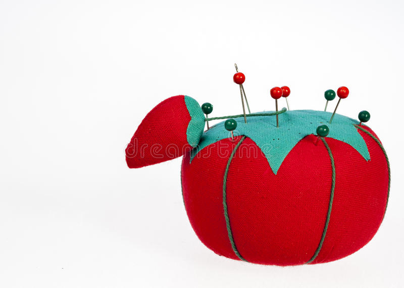 Red and green pincushion and pins stock photography