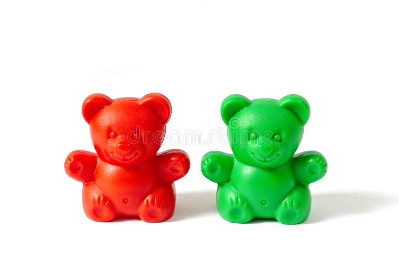 Red and green plastic toy bears isolated on white background. Small red and green plastic toy bears isolated on white background stock image