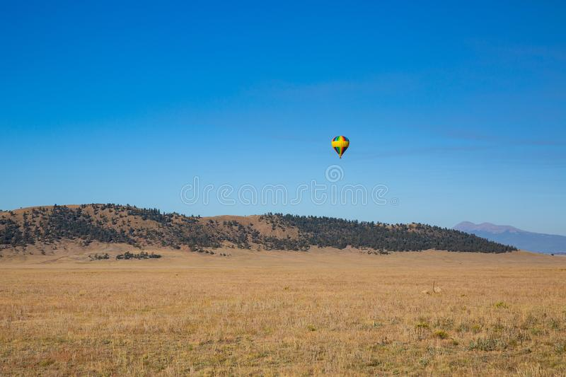A rainbow colored hot air ballon floats above a valley and mountains. stock photo