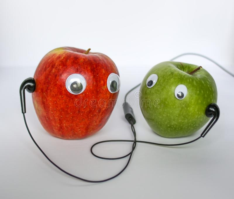 Red and green small apples with cute eyes and headphones on white background. Conceptual photo. stock image