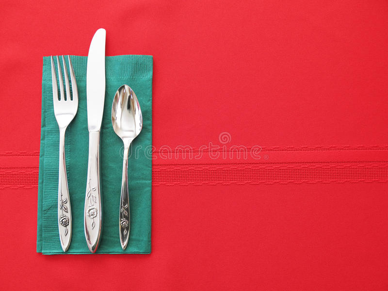 Red and Green Table Place Setting Background. Christmas colors red and green place setting background. Silverware with fork, knife, and spoon and napkin provide royalty free stock photos