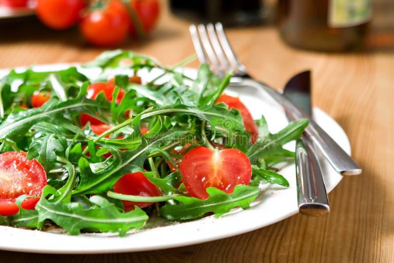 Red and green tomato-arugula salad stock image