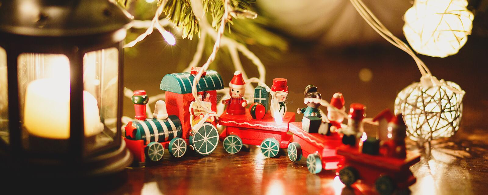 Red and green train stands under fir tree in lights next to black candlestick on the floor. Christmas and New year celebration stock image